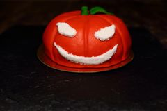 Cake on Halloween orange pumpkin. The idea for baking and decorating for Halloween. An ominous orange pumpkin with white eyes and a mouth. He smiles. On the royalty free stock photos