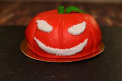 Cake on Halloween pumpkin. The idea for baking and decorating for Halloween. An ominous orange pumpkin with white eyes and a mouth. He smiles. On the pumpkin is royalty free stock image