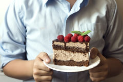 Cake in hands. Closeup hands holding piece of delicious chocolate cake with raspberries and mint in white plate Royalty Free Stock Photos