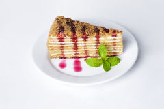Cake honey cake on a plate with mint and berry fruit raspberry sauce  white background Royalty Free Stock Photos