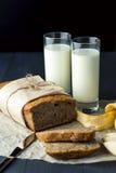 Cake à la banane avec des verres de lait sur le papier de cuisson Images stock