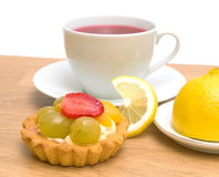 Cake, lemon and a cup of fruit tea on a white background. Cake with fruit, lemon and a cup of fruit tea close-up on white background Stock Photos