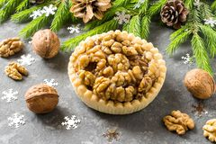 Cake with lemon jam and caramelized walnuts. Nut cake with lemon jam and caramelized walnuts. Decorated Christmas tree branches. Delicious Christmas dessert Stock Image