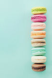 Cake macaron or macaroon on blue background from above. Colorful almond biscuits. Vintage card. Flat lay. Royalty Free Stock Image