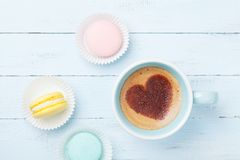 Cake macaron or macaroon and cup of coffee with heart on foam top view. Flat lay style. Stock Image