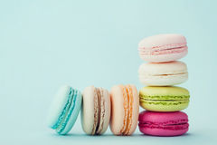 Cake macaron or macaroon on turquoise background, flavor almond cookies, pastel colors. Vintage card royalty free stock images