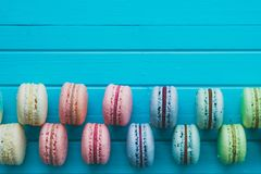 Cake macaron or macaroons lie on a wooden turquoise background in checkerboard pattern, top view close-up, copy space.  Stock Photo