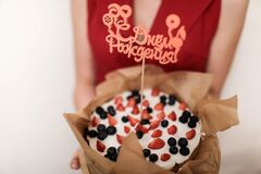 Cake made of berries with the inscription in Russian Happy Birthday.