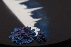 Cake made by professional chef, closeup. Black cake with white town silhouette and blue cornflower Stock Images