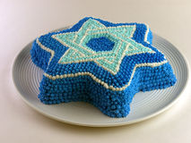Cake with Magen David (Star of David). A beautiful cake in the form of Star of David decorated blue and white colors. On a rond porcelain plate Stock Photos