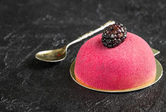 Cake with marzipan and spoon for breakfast on a concrete backgr. Mousse cake with blackberries for dessert on a dark background vertical Stock Photo