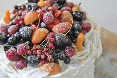 Cake meringues with fruits and berries. Currants, cherries, raspberries and apricots royalty free stock photo