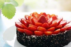 Cake met de aardbeihelften die wordt verfraaid Stock Foto