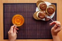 Cake met een kop thee op een donkere houten achtergrond Vrouwelijke handen op een achtergrond van cakes en een kop thee Stock Foto