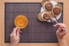 Cake met een kop thee op een donkere houten achtergrond Vrouwelijke handen op een achtergrond van cakes en een kop thee Royalty-vrije Stock Foto's