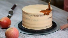 Cake met gezouten karamelsaus die wordt verfraaid stock videobeelden
