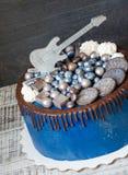Cake met snoepjes, koekjes, bosbessen en gitaar topper Stock Fotografie