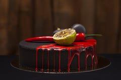 Cake met zwart fluweel wordt behandeld dat met kalk, Spaanse peperpeper en makarons, rode glans op bovenkant royalty-vrije stock afbeelding