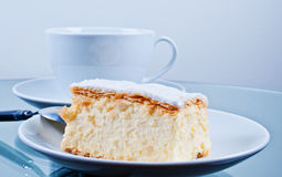 Cake Napoleon on table. With cup Royalty Free Stock Photography