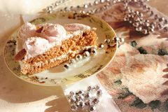 A piese of sponge cake covered with white icing. Decorated with pink roses and almonds with silver beads Royalty Free Stock Photo