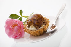 Cake with nuts and a beautiful rose. A delicious cake with nuts arranged on a plate with a spoon and a beautiful rose Stock Photos