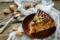 Cake with nuts, chocolate chips and chocolate glaze Stock Images