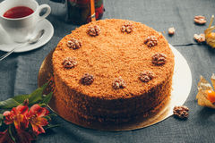 Cake with nuts. Image of a delicious chocolate and nut cake with teacups in the background royalty free stock photo