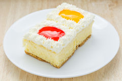 Cake, orange and strawberry flavored berries in white plate. Stock Image