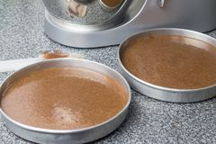 Cake pans with chocolate batter and mixer in background. Cake pans filled with raw chocolate batter and mixer on kitchen counter background stock photos