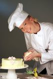 Cake Pastry Chef. Attractive female pastry chef in uniform piping pastry art on a cake Royalty Free Stock Photography