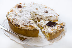 Cake. Pastry cake with cream, covered with almonds and icing sugar royalty free stock photography