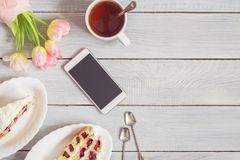 Cake, phone, cup of tea and pink tulips on white wooden table Royalty Free Stock Images