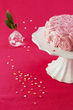 Cake on pink background. A decoration cake on a white cake stand and flower on pink background with sugar hearts Stock Photography