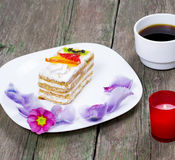 Cake on a plate a candle and the coffee decorated with flowers n Royalty Free Stock Photo