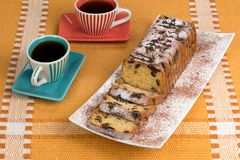 Cake on a plate with coffee. Cake with raisins and powdered sugar on a plate with coffee Stock Image