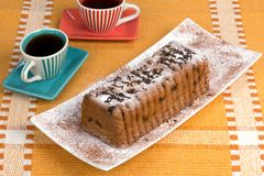 Cake on a plate with coffee. Cake with raisins and powdered sugar on a plate with coffee Royalty Free Stock Photos