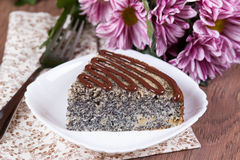 Cake with poppy seeds and chocolate. On the plate Royalty Free Stock Photos