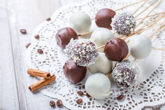 Cake pops decorated with white, dark chocolate and coconut on napkin, natural light. Selective focus stock images