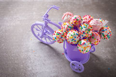 Cake pops  in decorative bicycle on grey slate  background. Royalty Free Stock Images