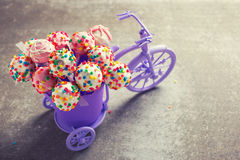 Cake pops  in decorative bicycle on grey slate  background. Royalty Free Stock Photos