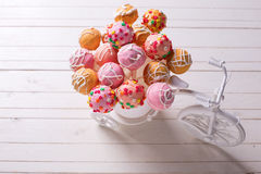 Cake pops  in decorative bicycle on white wooden background. Royalty Free Stock Images