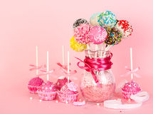 Cake pops with pink icing and decoration on paper form and color Royalty Free Stock Photos