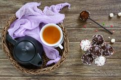 Cake pops. Round candy on a stick in chocolate glaze. A cup of tea Royalty Free Stock Image