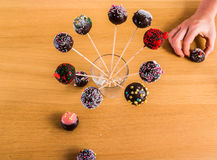 Cake-pops in stick in a glass with a helping hand Royalty Free Stock Photos