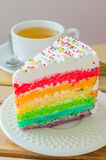 Cake. Rainbow cake with white tea cup on the wood table Royalty Free Stock Images