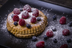 Cake with raspberries, blueberries, sea buckthorn sprinkled powdered sugar on a black plate Royalty Free Stock Image