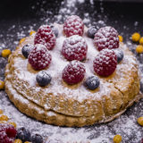 Cake with raspberries, blueberries, sea buckthorn sprinkled powdered sugar on a black plate Royalty Free Stock Images