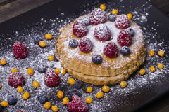 Cake with raspberries, blueberries, sea buckthorn sprinkled powdered sugar on a black plate Stock Photos
