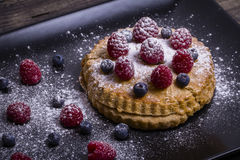 Cake with raspberries, blueberries, sea buckthorn sprinkled powdered sugar on a black plate Stock Photo