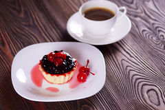 Cake with raspberries and currants. On a white plate with cherry. Jelly Bean. Coffee Stock Image